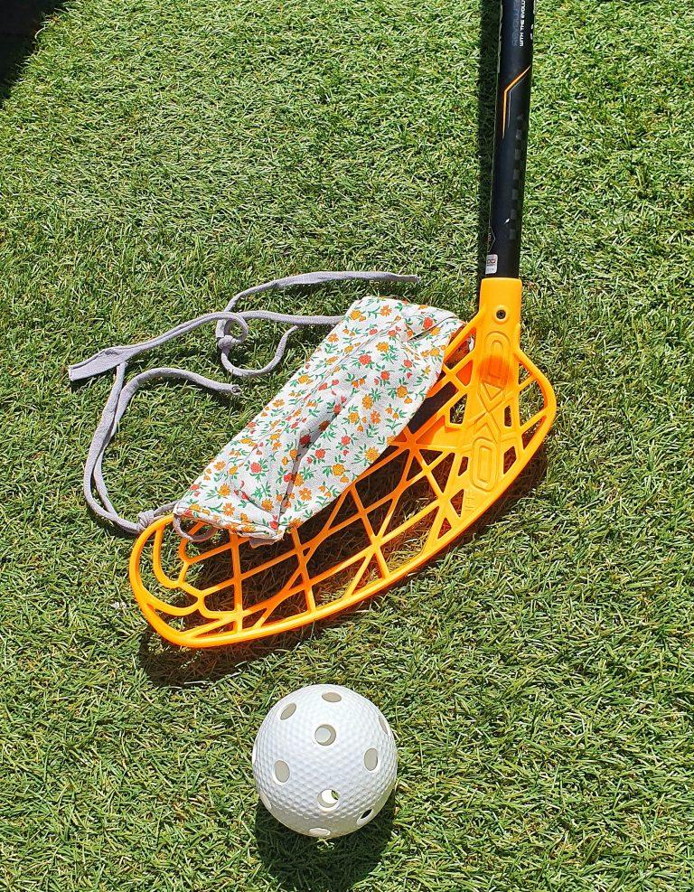 Ein Floorballschläger und Mundschutz auf dem Rasen